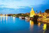 Golden Tower with cityscape and river of Sevilla at night Seville, Spain poster