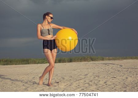 Vintage Styled Model Posing With Big Yellow Ball At The Beach