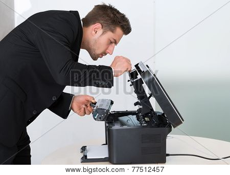 Young Businessman Fixing Cartridge In Photocopy Machine