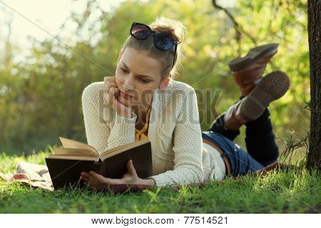 Close Up Portrait Of Reading Trendy Girl With Book Lying Beneath A Tree In The Evening