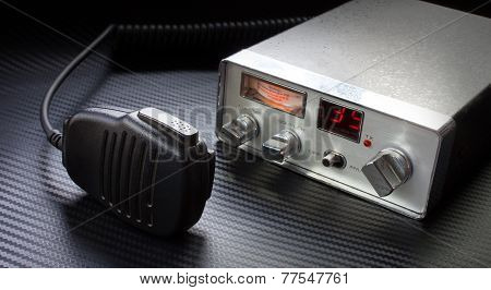 Old CB radio and microphone on a grey background poster