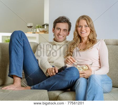 A couple after dinner watching tv with a bowl of popcorn