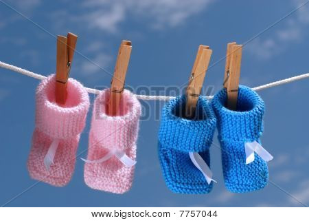 Pink & Blue Baby Booties Hanging On A Clothes Line