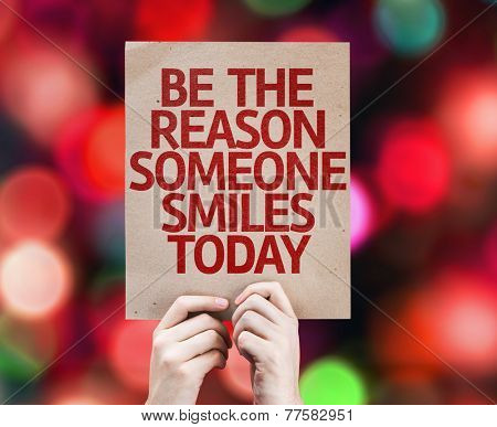 Be The Reason Someone Smiles Today card written on colorful background with defocused lights poster