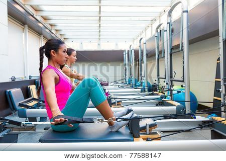 Pilates reformer workout exercises women at gym indoor