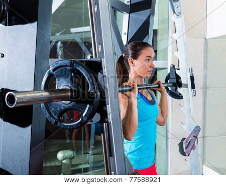 brunette girl in multipower barbell shoulder press Smith machine at gym poster