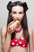 Skinny beautiful girl eating hotdog. pinup style poster