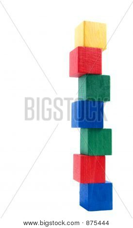 old fashioned wooden chldren building blocks arranged as precarious looking tower against a white background poster
