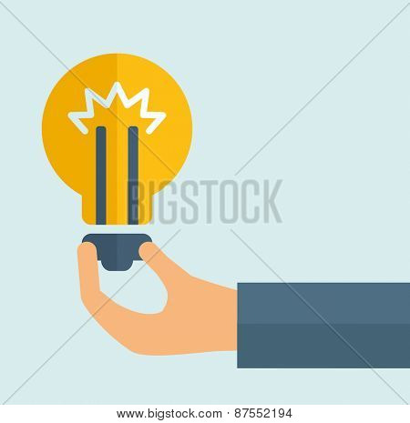 A hand holding colorful bright incandescent light bulb