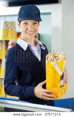 Portrait of beautiful female worker holding popcorn paperbag at cinema concession counter