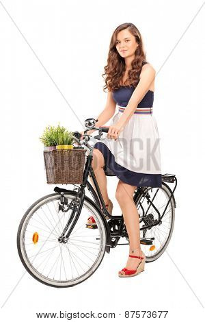 Beautiful young woman posing seated on a black bicycle with a basket in the front, carrying two flowerpots isolated on white background