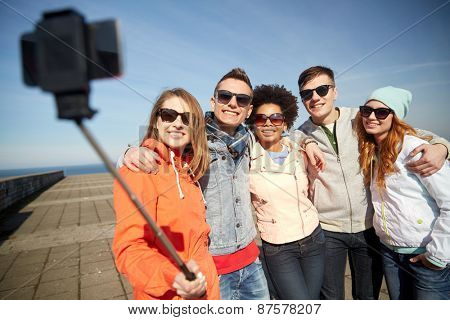 tourism, travel, people, leisure and technology concept - group of smiling teenage friends taking selfie with smartphone and monopod on city street poster