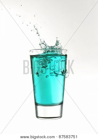 Splash in a glass of turquoise lemonade isolated on white background