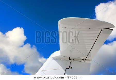 Tail Of A Aircraft With A Blue Sky And Clouds
