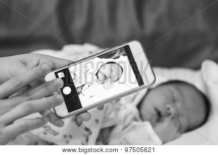 Asian Mother Take A Photo Of Her Baby Female Son With Smart Phone Black And White