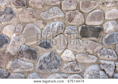 Gray pebble stones in a stone wall