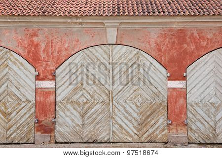 Weathered white painted wooden gates and the red wall of the stables next to Rundale, Latvia.
