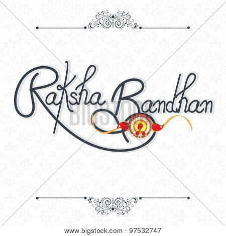 Greeting card dsign with stylish text Raksha Bandhan and beautiful rakhi on shiny background.