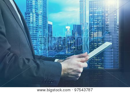 Close-up Of Side View Of A Businessman Who Is Browsing On His Tablet. Panoramic Manhattan Evening Vi