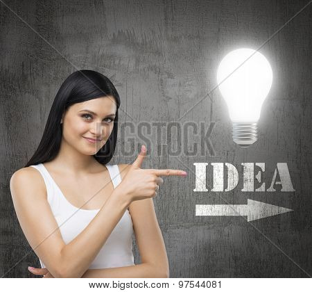 Brunette Woman Is In A White Tank Top. She Points Out The Lightbulb And The Word Idea With The Arrow