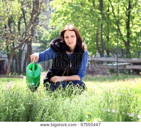 Woman In Gardening Waters Herbs