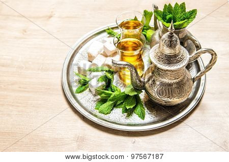 Tea with mint leaves and traditional turkish delight. Oriental hospitality concept. Holidays table setting. Ramadan kareem poster
