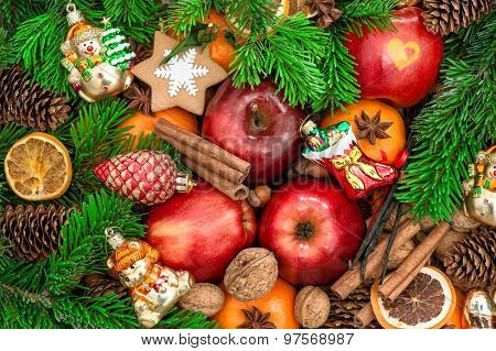 Christmas ornaments and decorations. Apples mandarin fruits walnuts cookies and spices with green tree branches poster