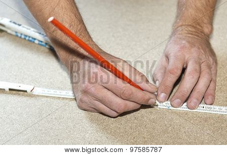 Man Uses A Yardstick To Mark The Chip Board