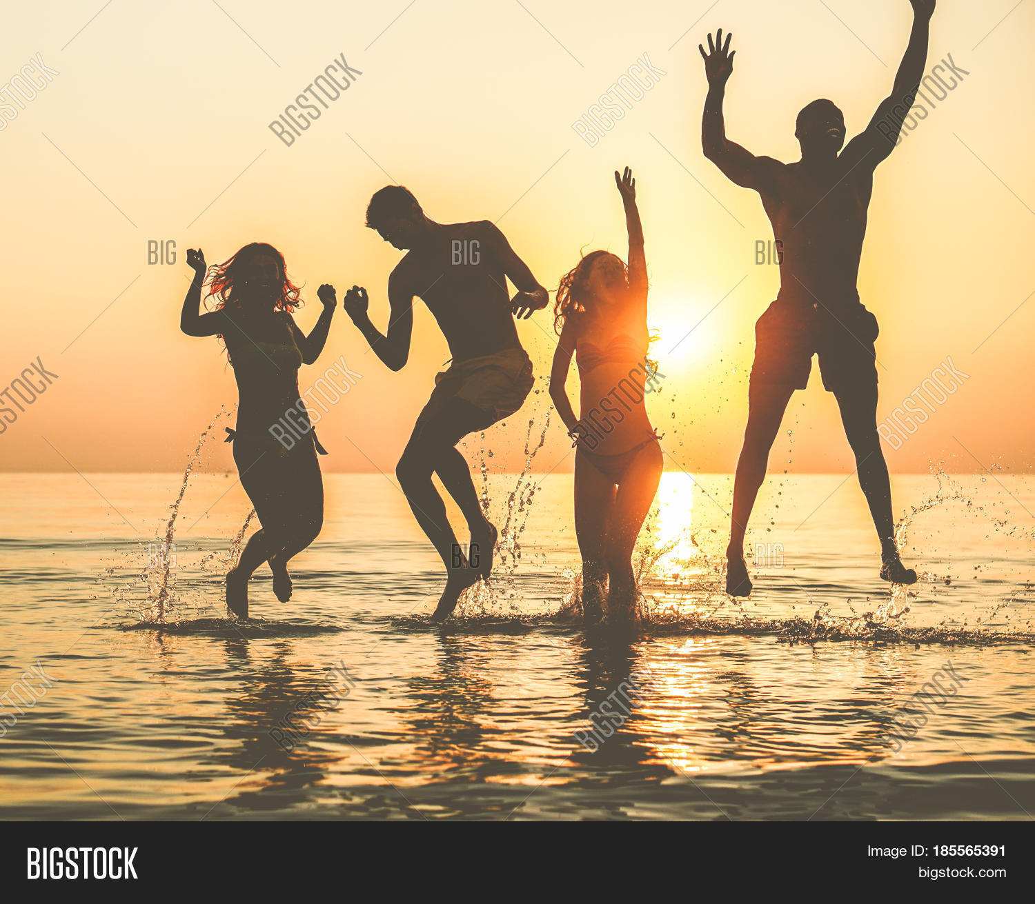 Silhouettes Of Happy Friends Jumping Inside Water On The Beach At Sunset