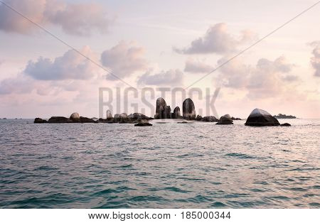 Natural Rock Formation In Sea At Belitung Island Early In The Morning With Violet Colored Clouds In