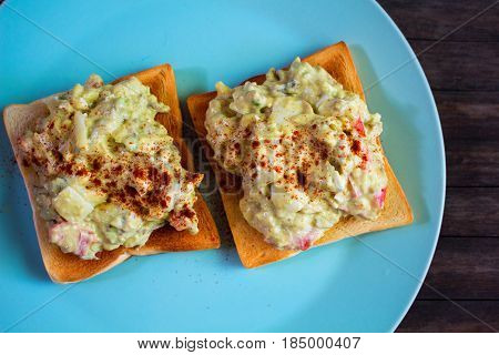 Two sandwiches with avocado salad on blue plate. Crunchy toast with vegetarian salad. Avocado and mayonnaise with egg and paprika. Healthy breakfast. Vegetarian fast-food. Whole-grain bread snack