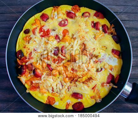 Omelette with tomato and sausage. Healthy nutritious food for man. Scrambled eggs with cheese meat and vegetables. Morning meal cook. Hot breakfast in rustic village style. Summer countryside dish