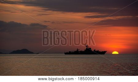 Silhouette of big ship on the ocean at nightfall with orange sunset at the background combined with a cloudy sky Labuan Bajo Bajawa.