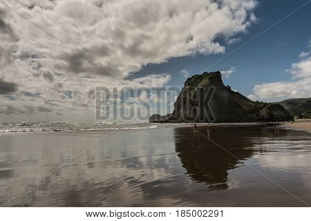 Auckland New Zealand - March 2 2017: Lion rock reflected in wet sandy Piha beach in Tasman Sea surf and under blue sky with white clouds. Some people.