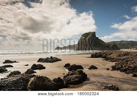 Auckland New Zealand - March 2 2017: Lion rock on Piha Beach of Tasman Sea surrounded by surf and under blue cloudy sky. Forefront is sand and dispersed black volcanic rocks.