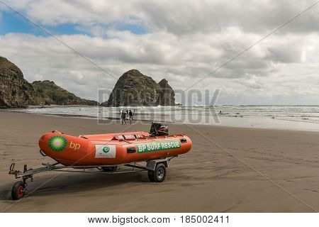 Auckland New Zealand - March 2 2017: Closeup of orange dinghy boat of beach life guard at Piha Beach with Rabbit rock in the back. Tasman sea surf and people.