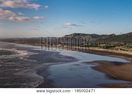 Auckland New Zealand - March 2 2017: Twilight wide shot photo of Muriwai Beach under blue sky reflected on wet beach invaded by Tasman Sea surf. Dunes mountains and more in back.