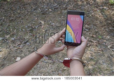 Smartphone addiction concept - boy shackled with a chain using a mobile phone.