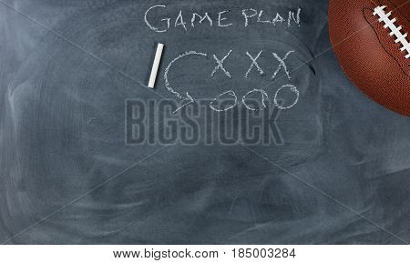Overhead view with American sport football on chalkboard with game plan. Horizontal format with copy space.