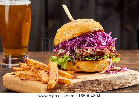 Sandwich with pulled pork, french fries and glass of beer on wooden background