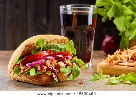 Sandwich with pulled pork, salad, tomato and glass of cola on stone table. Rustic style