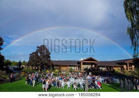 EUGENE, OR - SEPTEMBER 3, 2016: Rainbow stretching across the sky over a wedding ceremony at Shadow Hills Country Club.