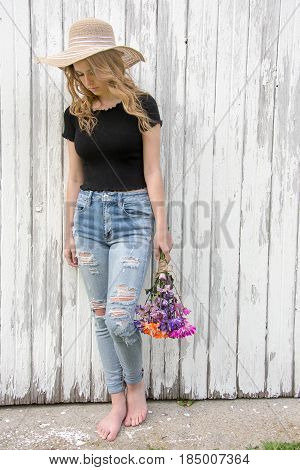 barefoot teenage girl with daisy bouquet and frayed jeans by whitewashed barn