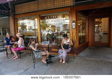 HARBOR SPRINGS, MICHIGAN / UNITED STATES - AUGUST 4, 2016: People enjoy eating Kilwin's ice cream, at tables outside of store's front window, during the Street Musique event on Main Street in downtown Harbor Springs.