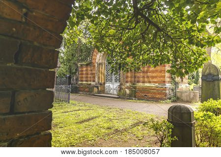 Look Through A Gate And Leaves To A Tomb
