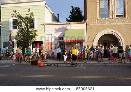 HARBOR SPRINGS, MICHIGAN / UNITED STATES - AUGUST 4, 2016: Crowds walk on the sidewalk and eat ice cream in front of Yummie's Ice Cream Store during the Street Musique event in downtown Harbor Springs.