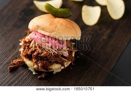 Slow cooked pulled pork with BBQ sauce pickled onions coleslaw and cheese served in a hamburger bun with dill pickle and chips as sides. It's a messy sandwich but so delicious!