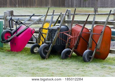 Wheel barrows put away leaning against fence outside of community garden.