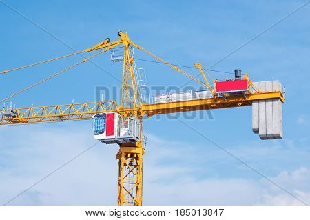 Crane in construction area against blue sky