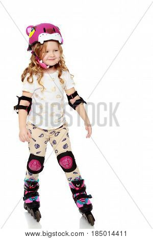 Beautiful, chubby little girl with long, blond, curly hair.Girl riding roller skates in protective gear.Isolated on white background.